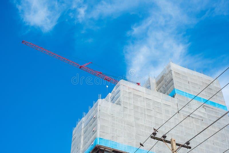 Cantiere del grattacielo con la gru sul fondo del cielo blu immagine stock libera da diritti