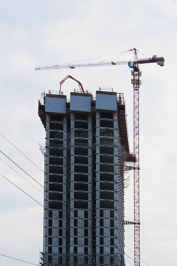 Cantiere di grattacielo moderno Sollevi la gru a torre ed il nuovo edificio residenziale in costruzione contro fotografie stock libere da diritti