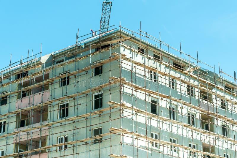 Cantiere di nuovo edificio residenziale con la gru e l'impalcatura fotografia stock libera da diritti