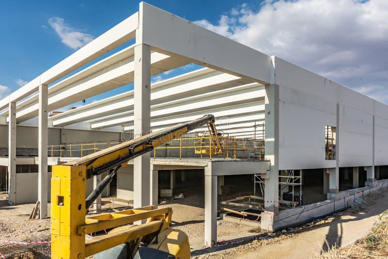 Cantiere di un magazzino industriale con un elevatore mobile fotografia stock