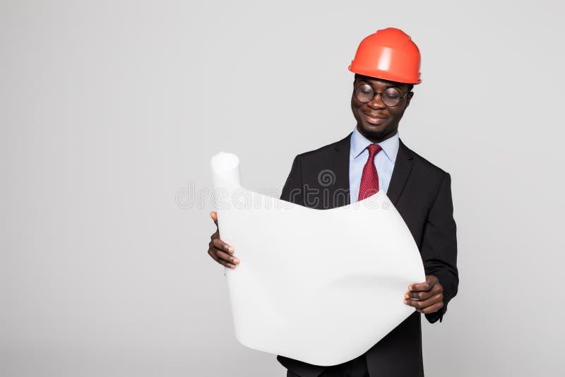 Cantiere di visita dell'architetto nero professionista con i piani del modello ed il casco protettivo di sicurezza isolati su bia immagini stock libere da diritti