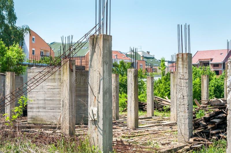 Cantiere non finito abbandonato della casa o della costruzione con i dettagli architettonici dei pali concreti a di rinforzo e de immagini stock