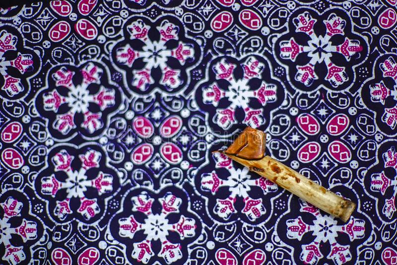 Canting and Batik. Tulis with purple fabric royalty free stock photo