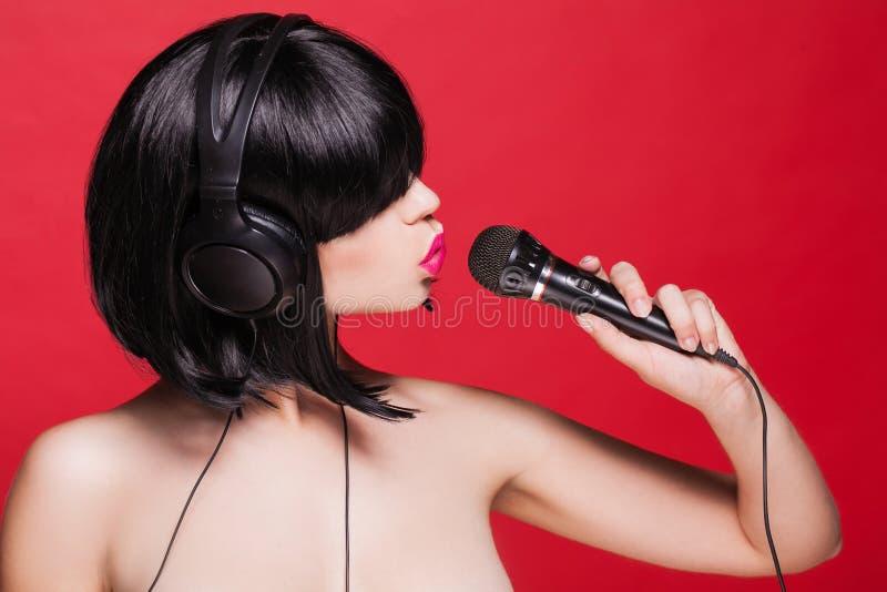 Canto alla moda della ragazza con un microfono, rosso fotografia stock