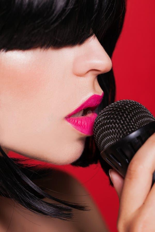 Canto alla moda della ragazza con un microfono, rosso immagini stock libere da diritti