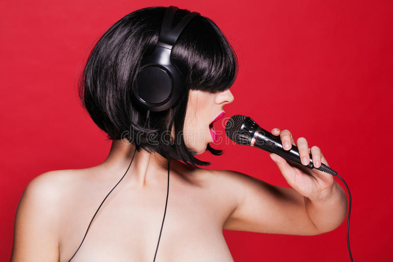 Canto alla moda della ragazza con un microfono su rosso immagini stock