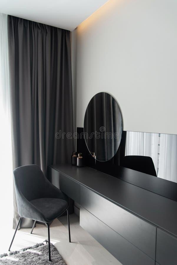 Canto da composição das mulheres com cadeira, tabela e espelho no quarto cinzento moderno no interior cinzento à moda fotos de stock royalty free