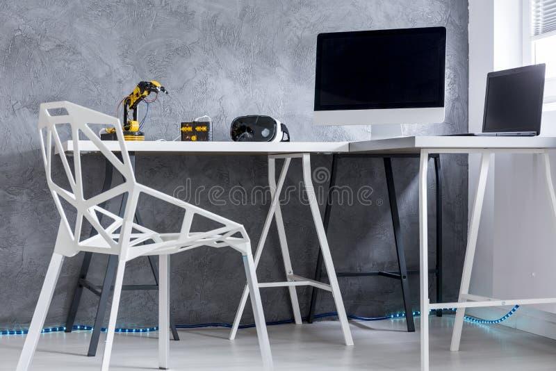 Canto da sala com cadeira e mesa com o computador imagens de stock royalty free