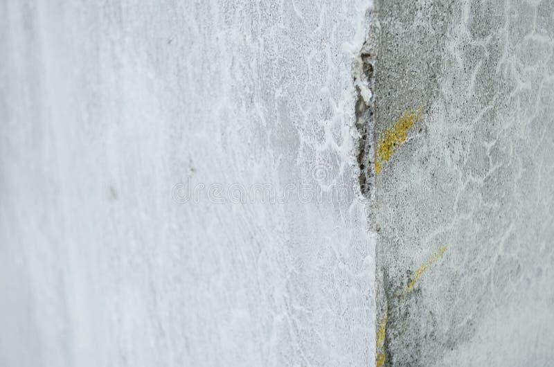 Canto de uma parede cinzenta quebrada do cimento, textura quebrada da parede do cimento do interior de uma casa foto de stock royalty free