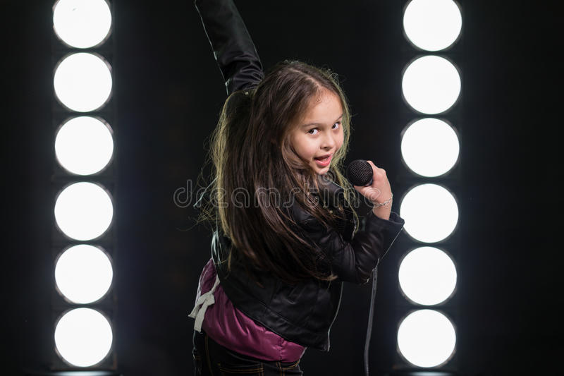 Canto della bambina davanti alle luci della fase fotografia stock