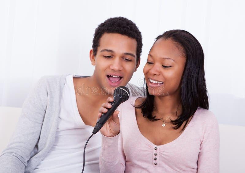 Canto delle coppie con il microfono fotografia stock libera da diritti