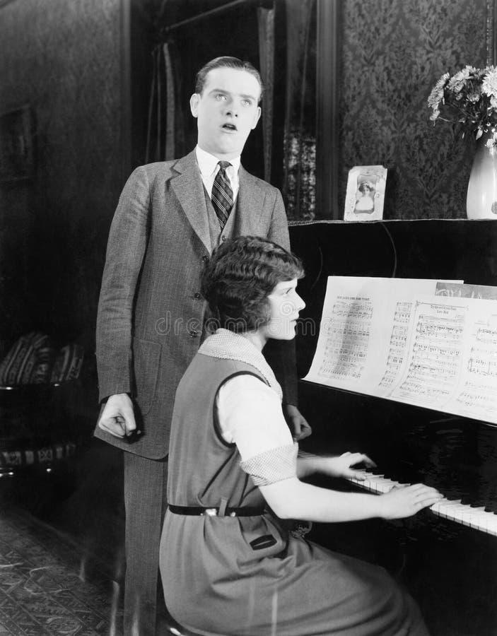 Canto e mulher do homem que jogam o piano (todas as pessoas descritas não são umas vivas mais longo e nenhuma propriedade existe  imagem de stock royalty free