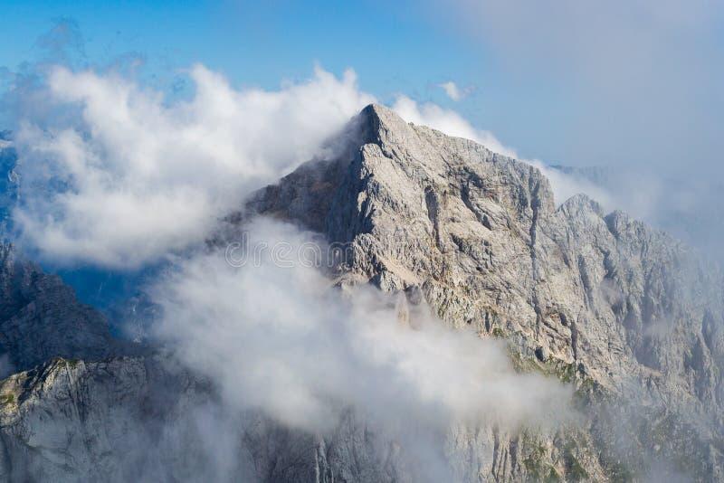 Canto en Julian Alps, parque nacional de Triglav, Eslovenia de Jalovec, con las nubes brumosas y el cielo azul El subir, alpinism foto de archivo libre de regalías