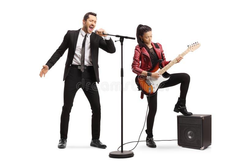 Canto maschio del cantante e una giovane donna che gioca una chitarra elettrica fotografie stock libere da diritti