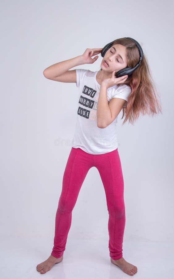 Canto que escucha de la muchacha y baile de una canción que escucha en las auriculares imagenes de archivo