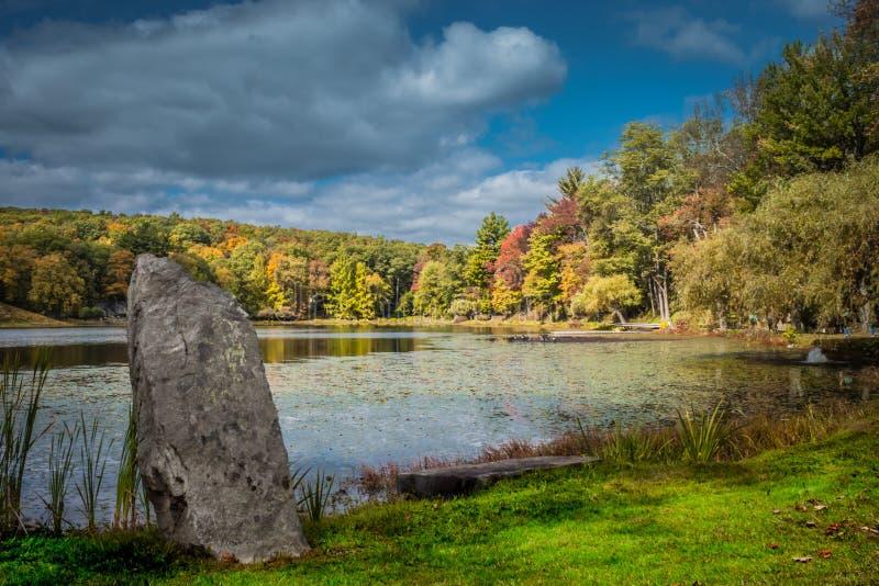 Canto rodado prominente exhibido debajo del cielo quebradizo dramático del otoño sobre el lago Tyrrel en el jardín de Innisfree,  fotos de archivo libres de regalías