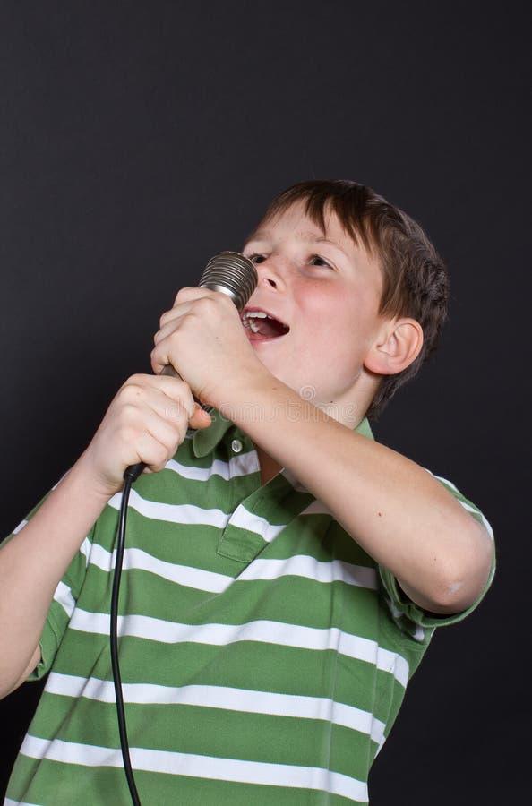 Canto Teenager In Un Microfono Immagini Stock