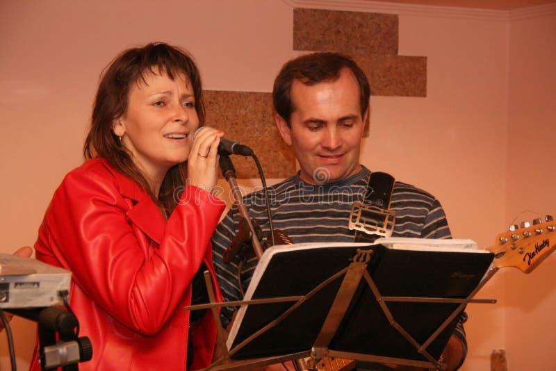 Canto y hombre de la mujer que juegan en la guitarra imagenes de archivo