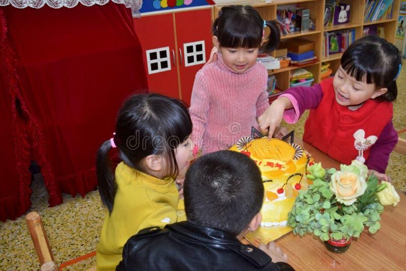 CANTONE, †della CINA «CIRCA MARZO 2019: Gruppo di bambini nell'asilo che si siede intorno ad una torta di compleanno per celebr immagini stock libere da diritti