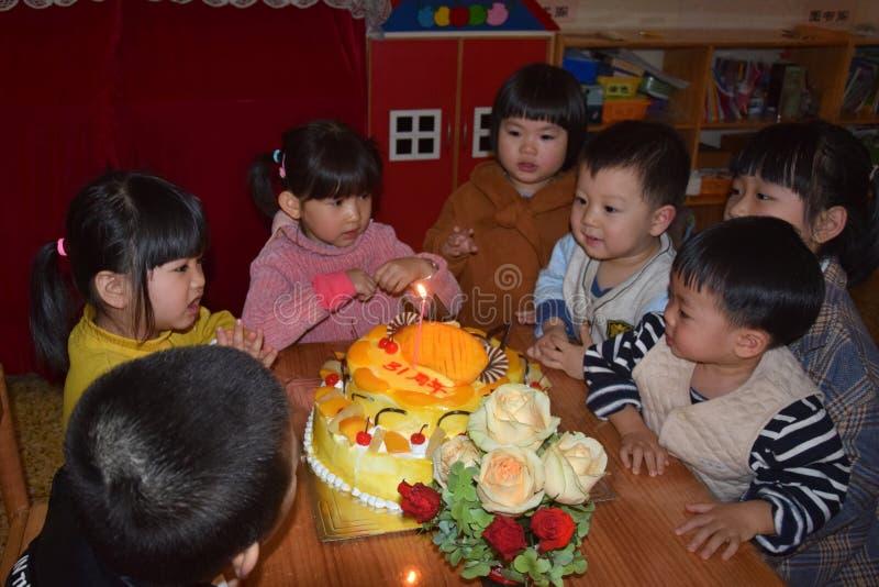 CANTONE, †della CINA «CIRCA MARZO 2019: Gruppo di bambini nell'asilo che si siede intorno ad una torta di compleanno per celebr fotografia stock
