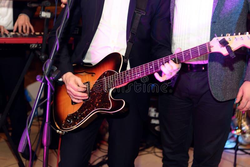 Cantor à moda do guitarrista que joga em uma fase com uma faixa no weddi imagens de stock