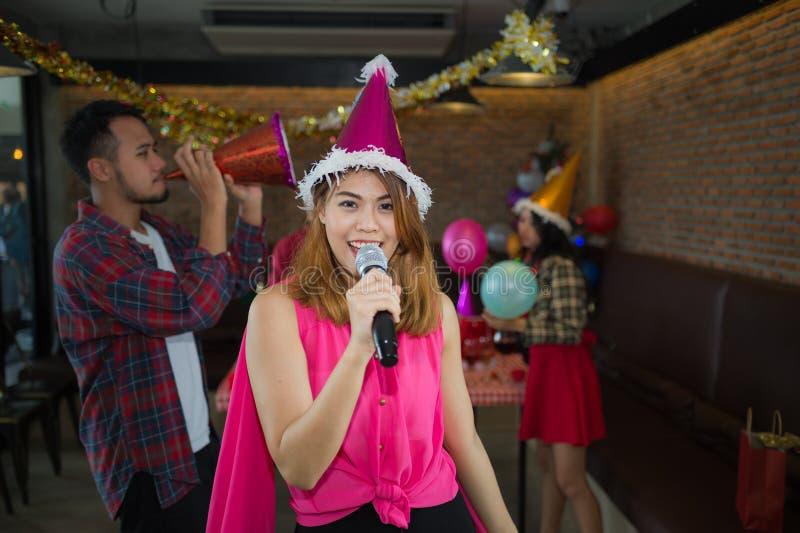 Cantor asiático da mulher no chapéu de Papai Noel com um microfone que canta foto de stock