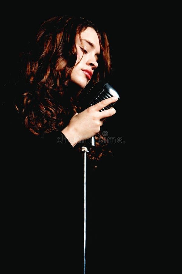 Cantor bonito que canta com microfone imagens de stock