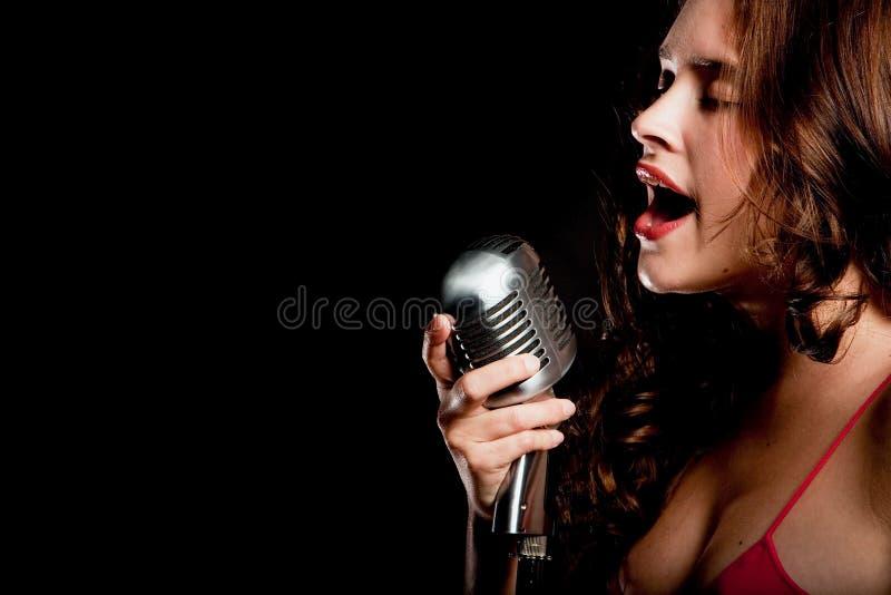Cantor bonito que canta com microfone fotos de stock royalty free