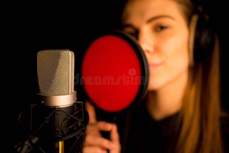 Cantor da mulher com os fones de ouvido que gravam no estúdio imagens de stock royalty free