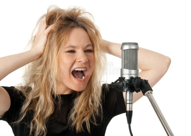Cantor de rocha que grita ao microfone fotografia de stock