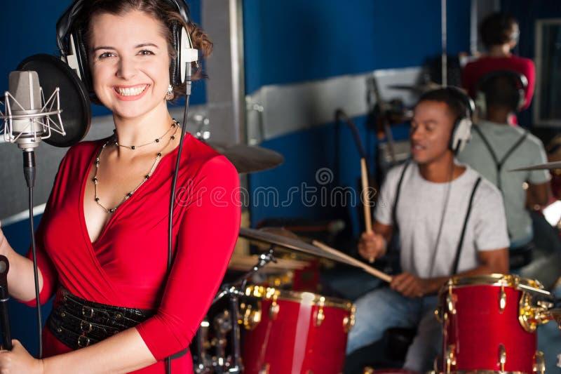 Cantor fêmea que grava uma trilha no estúdio fotografia de stock