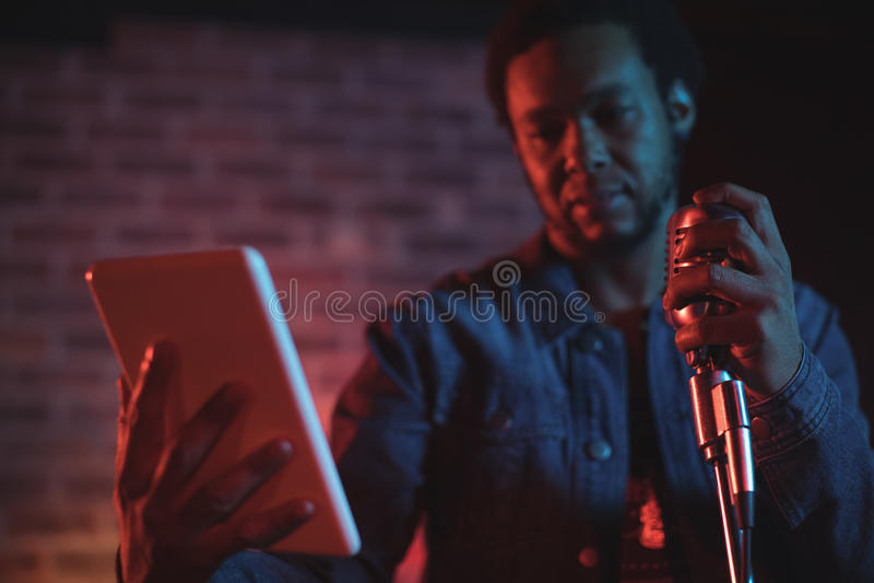 Cantor masculino que guarda a tabuleta digital ao executar no concerto da música imagem de stock royalty free