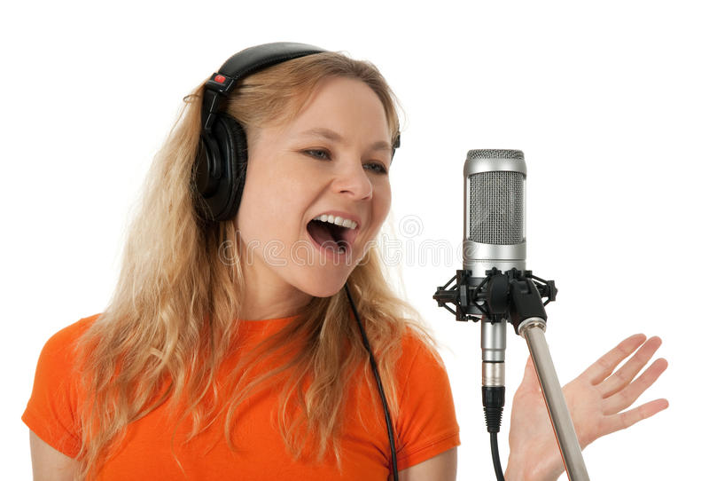 Cantor nos auscultadores que canta com o microfone imagem de stock