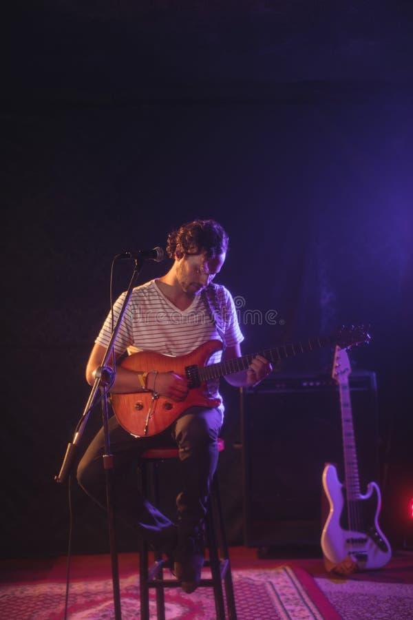 Cantor seguro que joga a guitarra ao executar no concerto imagens de stock royalty free