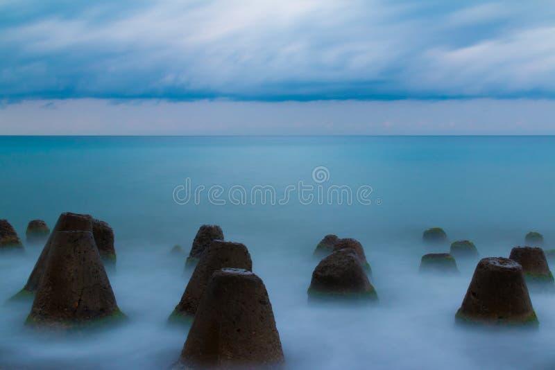 Cantos rodados concretos en el mar fotografía de archivo