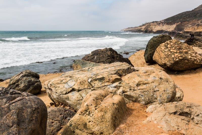 Cantos rodados y acantilados gigantes en las piscinas de Loma Tide del punto imagenes de archivo