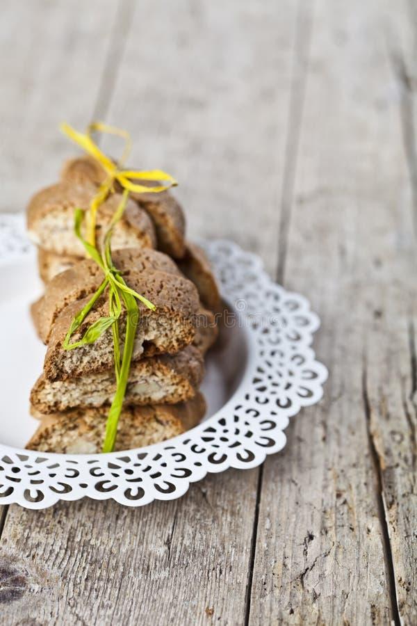 Cantuccini italiano hecho en casa fresco de las galletas apilado en la placa blanca en fondo de madera ructic de la tabla fotos de archivo libres de regalías