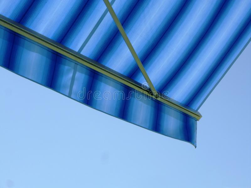 Canvas awning in blue and white under blue sky on a sunny summer day stock images