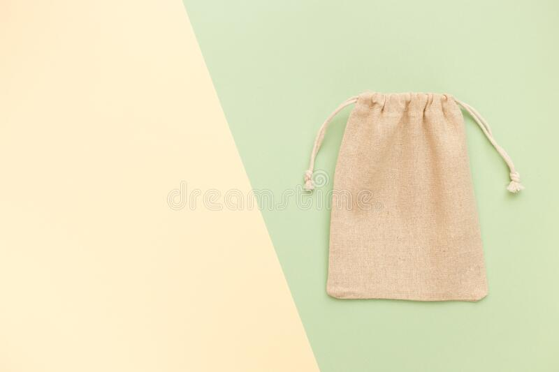 Canvas bag with drawstring, mockup of small eco sack made from natural cotton fabric cloth flat lay on green pastel background royalty free stock images