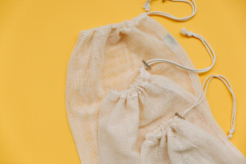 Canvas bag with drawstring, mockup of small eco sack made from natural cotton fabric cloth flat lay on yellow background top view royalty free stock images