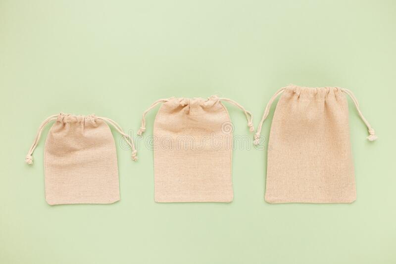 Canvas bags with drawstring, mockup of small eco sack made from natural cotton fabric cloth flat lay on green pastel background stock image