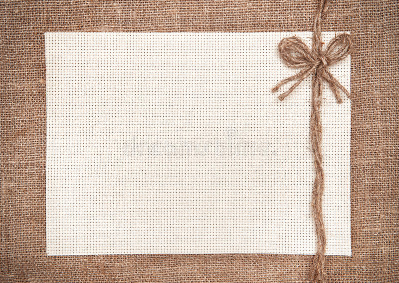 Canvas card on hessian background. Canvas card with rope bow on hessian background stock photo
