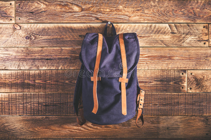 Canvas and leather backpack. On wooden wall royalty free stock photography