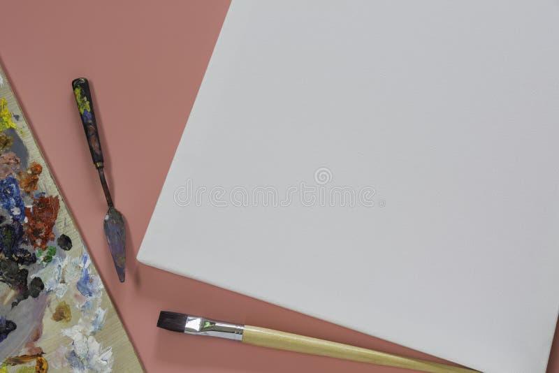 Canvas met borstels voor het materiaal van kunstenaarsArtistic en leeg canvas royalty-vrije stock fotografie