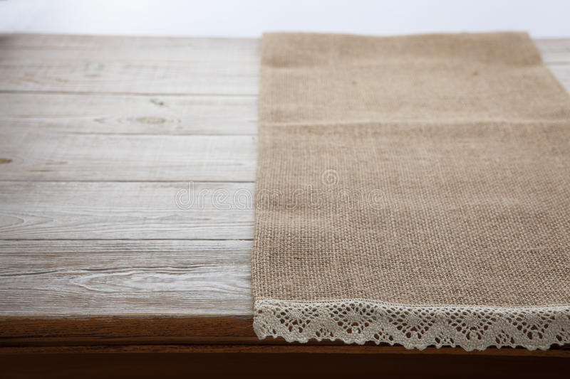 Canvas napkin with lace. Burlap hessian sacking on white wooden table background top view. Burlap hessian sacking on white wooden table top view stock image