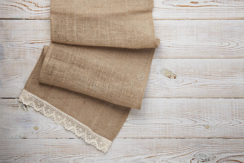 Canvas napkin with lace. Burlap hessian sacking on white wooden table background top view. Burlap hessian sacking on white wooden table top view royalty free stock photos