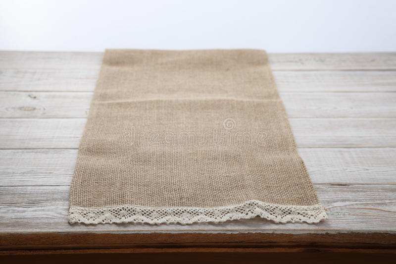 Canvas napkin with lace. Burlap hessian sacking on white wooden table background top view. Burlap hessian sacking on white wooden table top view royalty free stock photo