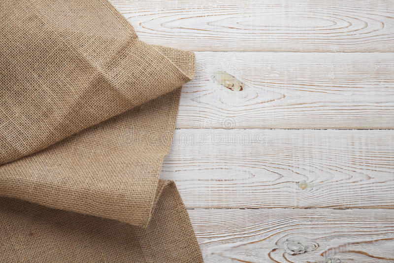 Canvas napkin with lace. Burlap hessian sacking on white wooden table background top view. Burlap hessian sacking on white wooden table top view royalty free stock image