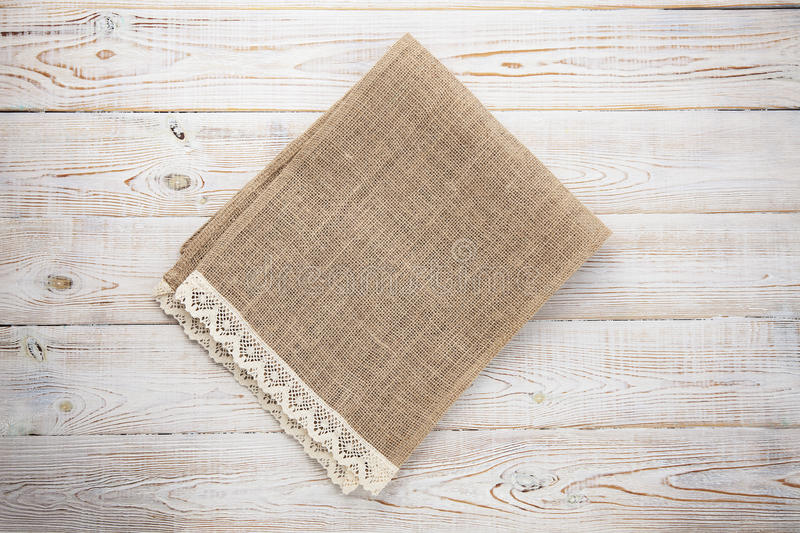 Canvas napkin with lace. Burlap hessian sacking on white wooden table background top view. Burlap hessian sacking on white wooden table top view royalty free stock photography