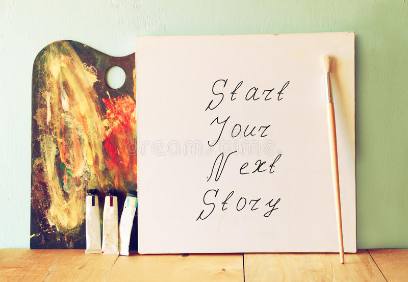 Canvas with the phrase start your next story next to oil paints and palette.  stock photos